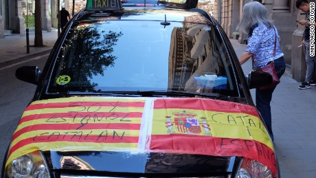 "A car is adorned with Spanish and Catalan flags reading ""I am Spanish and Catalan"" and ""I am Catalan and Spanish."""