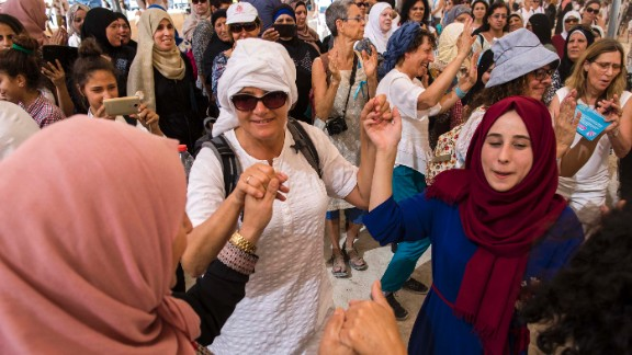 Israeli and Palestinian women dance together under a large tent during the mass protest.