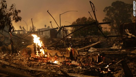 Flames rise from the remains of a burned commercial building in Santa Rosa, California, on Monday.