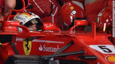 End of the road? Vettel is surrounded by Ferrari mechanics in the pit garage at Suzuka.