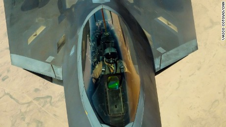 The pilot of an F-22 fighter jet looks up at the boom operator of a KC-10 Extender as his plane is refueled in mid-air over the Middle East.