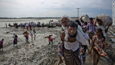 FILE - In this Friday, Sept. 29, 2017, file photo, a Rohingya Muslim man from Myanmar carries an elderly woman after they crossed the border into Bangladesh from Myanmar, in Teknaf, Bangladesh. More Rohingya Muslims fleeing violence in Myanmar are streaming toward the border, despite government assurances that it is succeeding in stopping the exodus of refugees into Bangladesh. (AP Photo/Gemunu Amarasinghe, File)