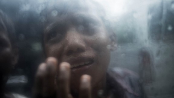A young Rohingya refugee begs for food through the glass of a car window at Balukhali refugee camp in Bangladesh on October 7.