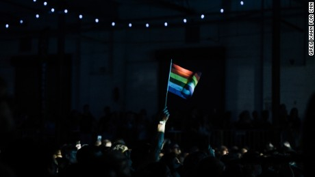"A fan waves a rainbow flag during Betty Who's performance at the ""All Things Go Fall Classic"" music festival at Union Market in Washington, DC on Oct. 8, 2017"