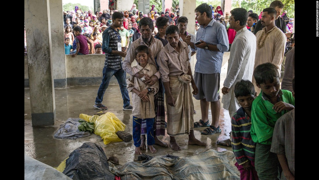 "Rohingya refugees mourn beside the bodies of relatives who died <a href=""http://www.cnn.com/2017/09/29/asia/rohingya-refugee-boat-capsize/index.html"">when a boat capsized</a> in late September."