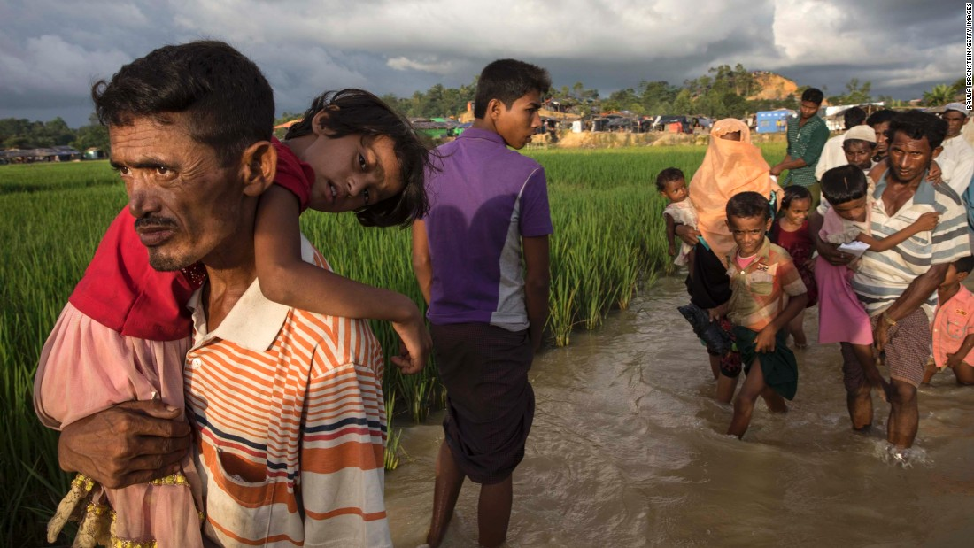 Rohingya refugees carry their belongings across muddy waters at a camp on October 5.