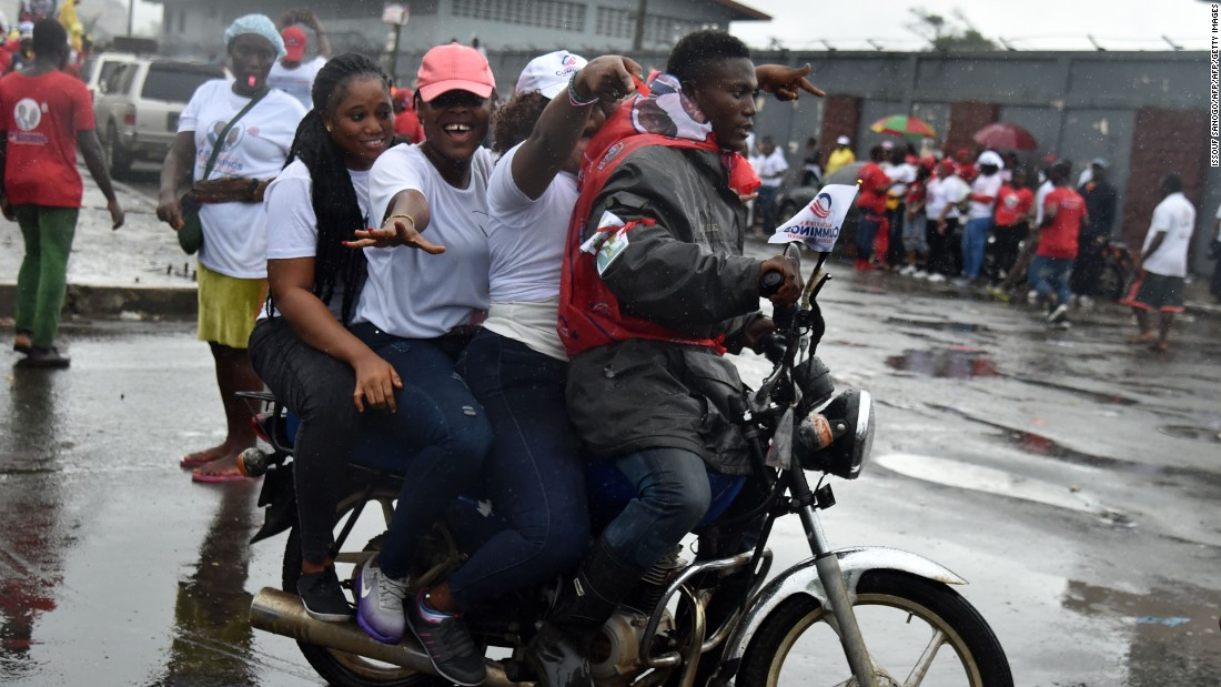 Supporters of Liberian presidential candidate Alexander Cummings arrive on a motorcycle to attend a campaign rally in Monrovia on October 7, 2017, three days ahead of the country's elections.