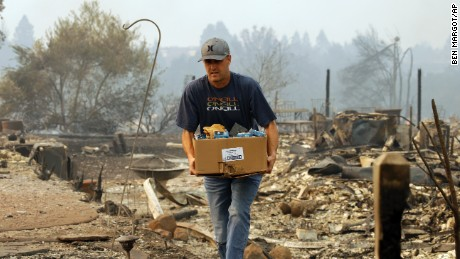 A man retrieves belongings from  where his house once stood in the Fountaingrove area of Santa Rosa.