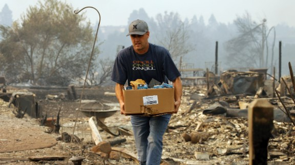 A man retrieves belongings from a safe where his house once stood in the Fountaingrove area of Santa Rosa, Calif., on Monday, Oct. 9, 2017. Wildfires whipped by powerful winds swept through Northern California early Monday, sending residents on a headlong flight to safety through smoke and flames as homes burned.