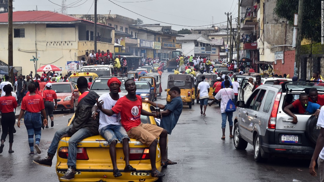Supporters of Liberian presidential candidate Alexander Cummings arrive atop a car to attend a campaign rally in Monrovia on October 7, 2017, three days ahead of the country's elections.