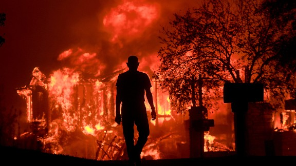 Jim Stites watches part of his neighborhood burn in Fountaingrove, Calif., Monday Oct. 9, 2017. More than a dozen wildfires whipped by powerful winds been burning though California wine country. The flames have destroyed at least 1,500 homes and businesses and sent thousands of people fleeing. (Kent Porter/The Press Democrat via AP)