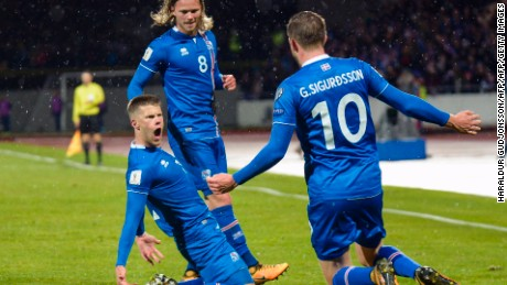 Iceland's forward Johann Berg Gudmundsson (L) celebrates scoring with his team-mates Iceland's midfielder Birkir Bjarnason (C) and Iceland's midfielder Gylfi Sigurdsson (R) during the FIFA World Cup 2018 qualification football match between Iceland and Kosovo in Reykjavik, Iceland on October 9, 2017.