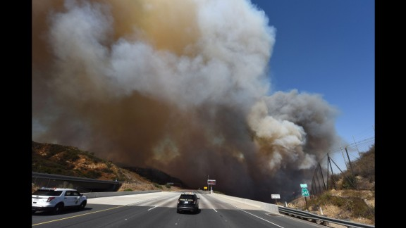 Police cars block the 241 freeway as smoke rises above Orange, California, on October 9.
