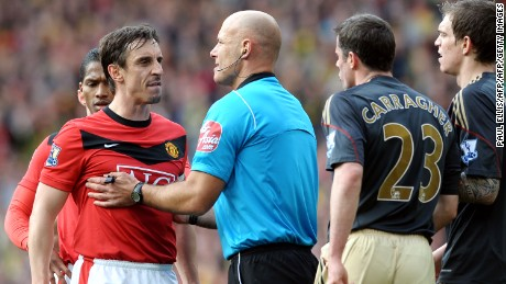 Referee Howard Webb holds United's Gary Neville away from Liverpool's defender Jamie Carragher during a United v Liverpool match at Old Trafford.