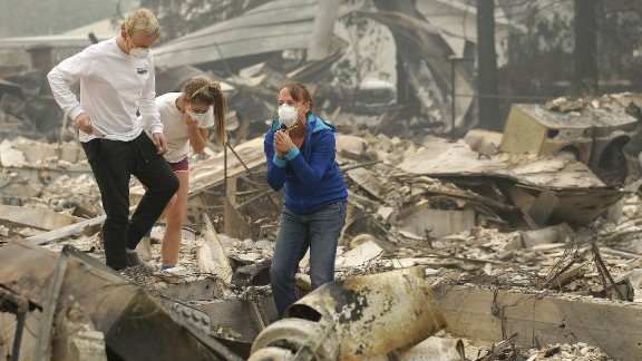 Mary Caughey, in blue, reacts after finding her wedding ring in debris at her destroyed home in Kenwood, California, on October 10.