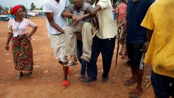 An elderly man is rushed to the Liberian government hospital in Buchanan, after he fainted due to the long, hot wait in a queue outside the Fairground Community polling station in Grand Bassa County. Credit: Local Voices Liberia/Elton Tiah