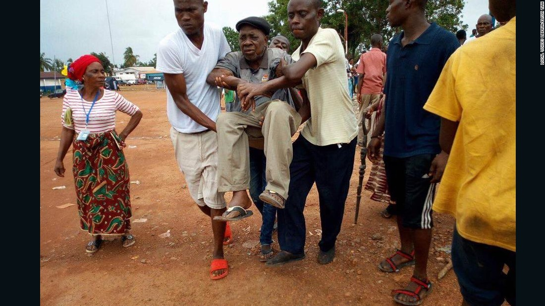 An elderly man is rushed to the Liberian government hospital in Buchanan, after he fainted due to the long, hot wait in a queue outside the Fairground Community polling station in Grand Bassa County.<br />Credit: Local Voices Liberia/Elton Tiah
