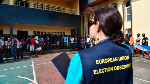A European Union election observer stands near voters queuing at a polling station in Monrovia.  Credit: Getty images