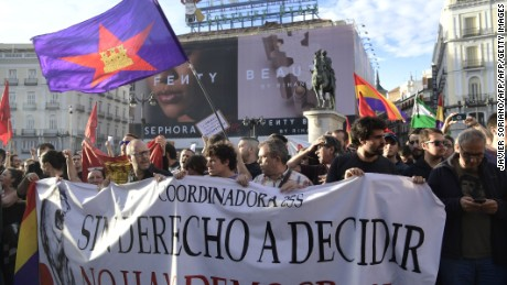 "Protesters hold a banner reading ""Without the right to decide there's no democracy"" as they gather at Puerta del Sol square during a demonstration in support of the right to hold a referendum on self-determination in Catalonia and against repression, in Madrid on October 1, 2017.  Several left-wing Spanish politicians today demanded Prime Minister Mariano Rajoy resign after police used force to block voting in a banned independence referendum in Catalonia, injuring dozens of people.  / AFP PHOTO / JAVIER SORIANO        (Photo credit should read JAVIER SORIANO/AFP/Getty Images)"