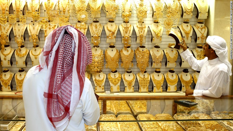 A gold merchant entices a potential customer with his jewelry at the Dubai Gold Souk in Dubai.