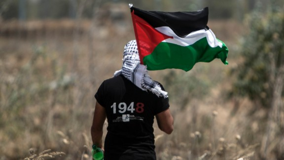 "TOPSHOT - A Palestinian youth waves the national flag as Israeli military digs in search of smuggling tunnels at the border east of Gaza city on May 15, 2016, on the 68th anniversary of the ""Nakba"". ""Nakba"" means in Arabic ""catastrophe"" in reference to the birth of the state of Israel 68-years-ago in British-mandate Palestine, which led to the displacement of hundreds of thousands of Palestinians who either fled or were driven out of their homes during the 1948 war over Israel's creation.  / AFP / MAHMUD HAMS        (Photo credit should read MAHMUD HAMS/AFP/Getty Images)"
