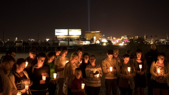 LAS VEGAS, NV - OCTOBER 3: At the corner of Sunset Road and Las Vegas Blvd., mourners attend a candlelight vigil for the victims of Sunday night's mass shooting, October 3, 2017 in Las Vegas, Nevada. Late Sunday night, a lone gunman killed over 50 people and injured over 500 people after he opened fire on a large crowd at the Route 91 Harvest country music festival. The massacre is one of the deadliest mass shooting events in U.S. history. (Photo by Drew Angerer/Getty Images)
