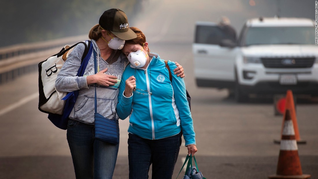Colby Clark, left, comforts her mother, Bonnie Trexler, after law enforcement escorted them to Trexler's home in Napa, California, to retrieve medicine and personal items on Wednesday, October 11. Trexler was one of the lucky few in her neighborhood whose home was spared. Deadly wildfires have been tearing through the state, destroying homes and businesses and prompting evacuation orders.