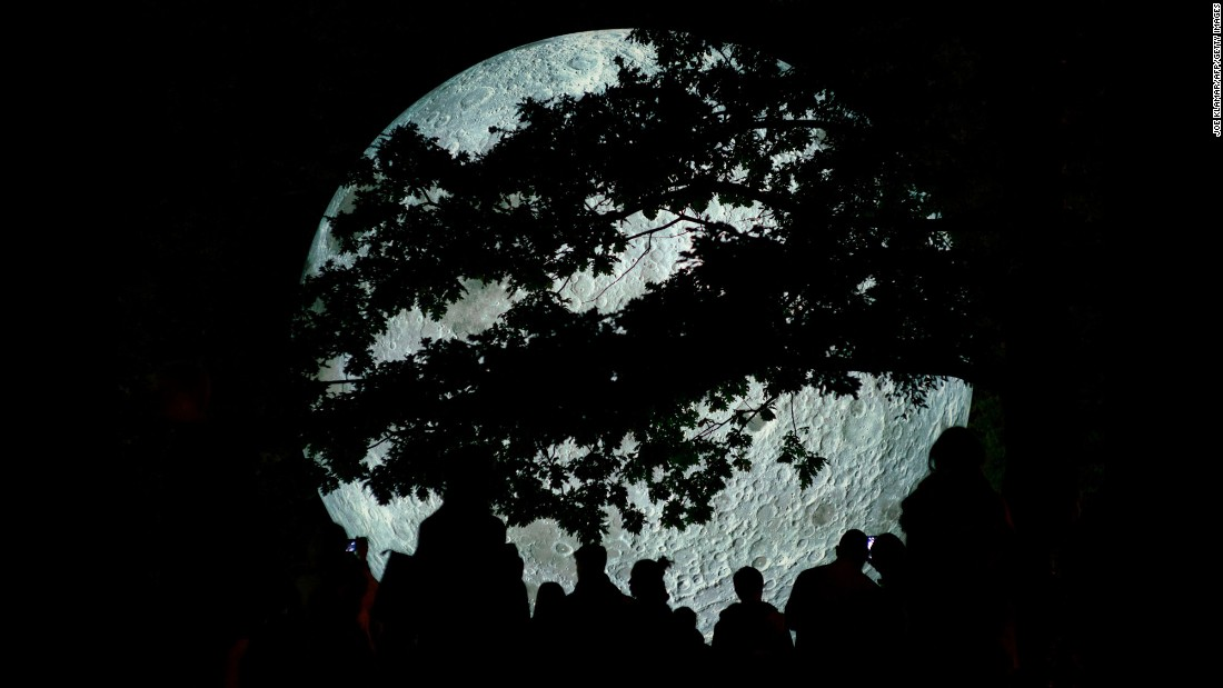 "People watch ""Museum of the Moon,"" an installation by British artist Luke Jerram, as it is displayed at the Medical Garden in Bratislava, Slovakia, on Saturday, October 7. The artwork features detailed NASA images of the moon's surface."