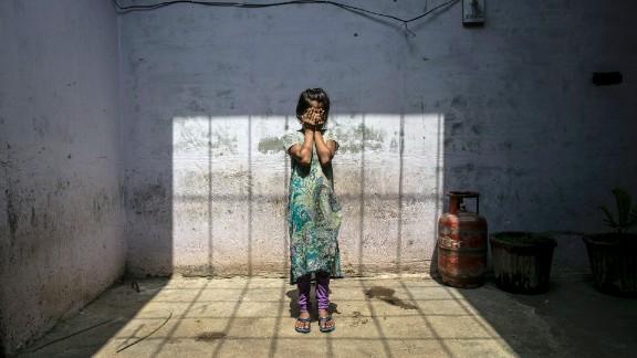 A child rape survivor stands in her home, in Uttar Pradesh, India, 2016.
