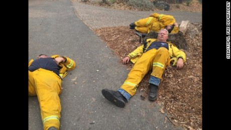 Firefighters with the Sebastopol Fire Department use the ground and a rock as a bed to get some rest.