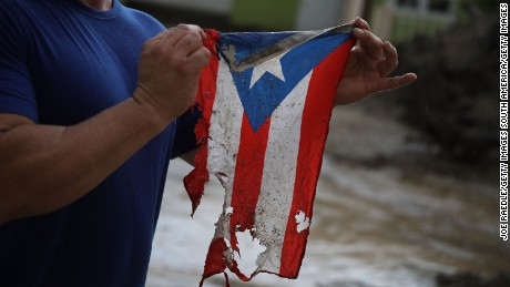 UTUADO, PUERTO RICO - OCTOBER 06:  Jose Javier Santana holds a Puerto Rican flag he found on the ground after Hurricane Maria passed through on October 6, 2017 in Utuado, Puerto Rico.  Mr. Santana said that the flag in its torn and frayed shape is how Puerto Rico is now.  (Photo by Joe Raedle/Getty Images)
