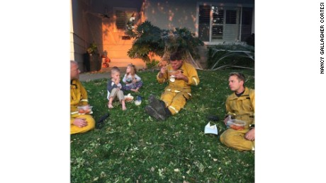 Firefighters take a break and eat a home cooked meal.
