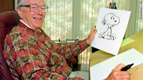"FILE - In this Feb. 12, 2000, file photo, cartoonist Charles Schulz displays a sketch of his beloved character ""Snoopy"" in his office in Santa Rosa, Calif. The home of ""Peanuts"" creator Schulz burned to the ground in the deadly California wildfires but his widow escaped, her stepson said Thursday, Oct. 12, 2017. Jean Schulz, 78, evacuated before flames engulfed her hillside home Monday and is staying with a daughter, Monte Schulz said. (AP Photo/Ben Margot, File)"