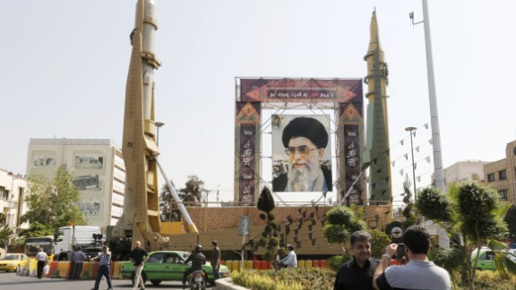 Iranians walk past Sejjil (L) and Qadr-H medium range ballistic missiles displayed next to a portrait of Iranian Supreme Leader Ayatollah Ali Khamenei on the occasion of the annual defence week which marks the anniversary of the 1980s Iran-Iraq war, on September 25, 2017, on Baharestan square in Tehran. (ATTA KENARE/AFP/Getty Images)