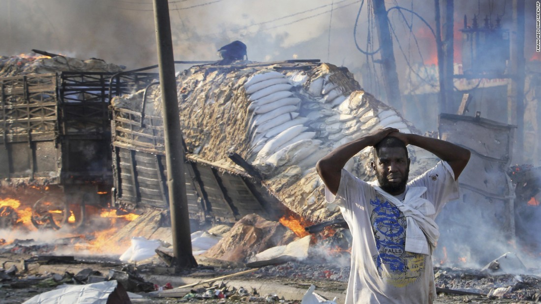 A Somali man reacts after seeing a body and destroyed buildings.