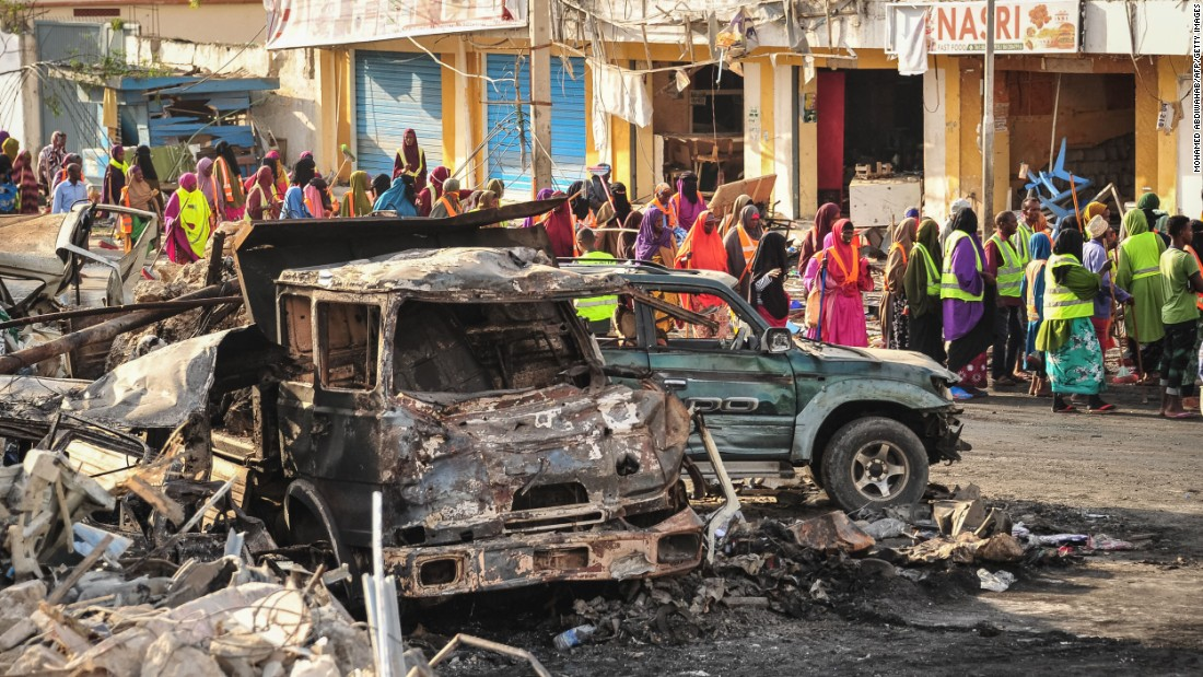 People gather near burnt vehicles a day after the explosions.