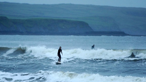 A woman surfs on Lahinch Strand in County Clare, Ireland, on October 15, 2017 -- the eve of Ophelia's arrival.