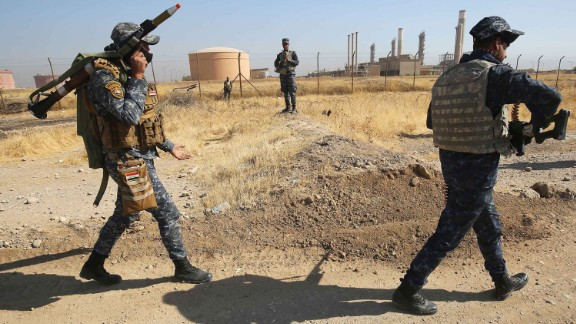 Iraqi forces pass an oil production plant Monday as they head toward Kirkuk.