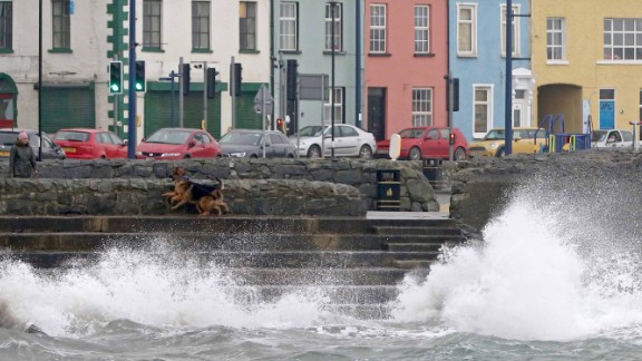 A woman walks her dogs along the sea in the coastal village of Donaghadee, Northern Ireland, on October 16, 2017.