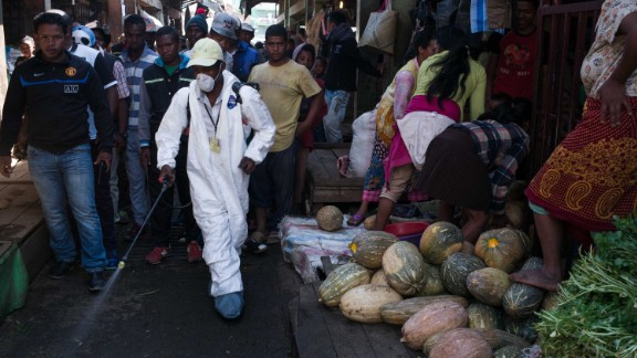 People stand back as a council worker sprays disinfectant during the clean-up of the market of Anosibe in the Anosibe district, one of the most unsalubrious districts of Antananarivo.