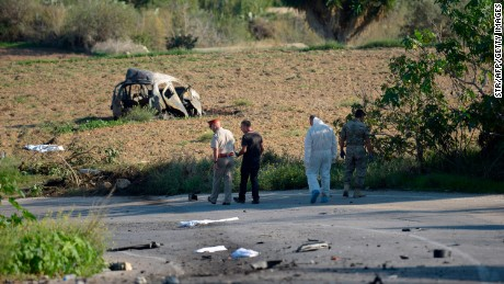 Police and forensic experts inspect the wreckage of the car following the explosion on Monday.