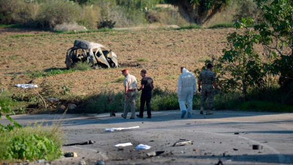 Police and forensic experts inspect the wreckage of a car bomb believed to have killed journalist and blogger Daphne Caruana Galizia.