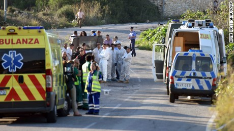 An ambulance is parked along the road where a car bomb exploded, killing investigative journalist Daphne Caruana Galizia.