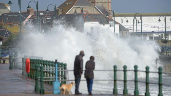 A couple watch waves break on the sea wall at Penzanze, southwestern England, on October 16, 2017.