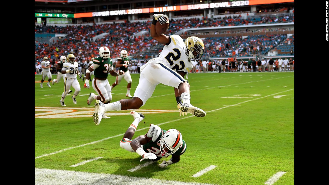 Miami Hurricanes defensive back Michael Jackson leaps over Georgia Tech Yellow Jackets running back Clinton Lynch during the first half of the game on Saturday, October 14, in Miami Gardens, Florida.