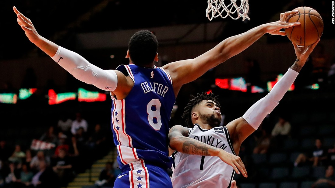 Brooklyn Nets guard D'Angelo Russell shoots as Philadelphia 76ers center Jahlil Okafor gets his fingers on the ball during the fourth quarter of a preseason NBA basketball game on Wednesday, October 11, in Uniondale, New York.