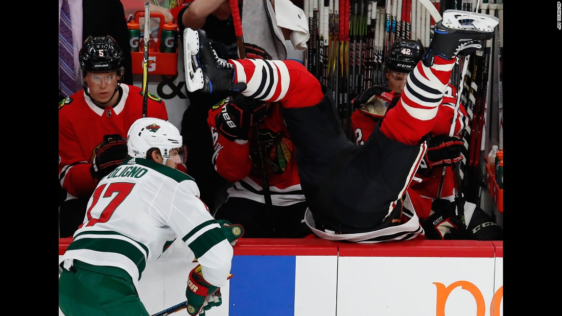 Chicago Blackhawks' Brent Seabrook, right, goes over the boards after missing a check on Minnesota Wild's Marcus Foligno during the first period of an NHL hockey game on Thursday, October 12, in Chicago.