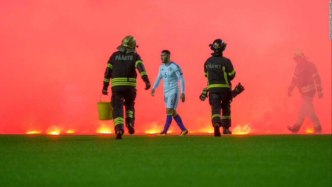 Firefighters run on the pitch to take care of flares thrown by Bosnia fans during the FIFA World Cup 2018 qualification soccer match between Estonia and Bosnia on Tuesday, October 10, in Tallinn, Estonia.