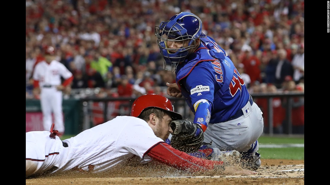 Willson Contreras of the Chicago Cubs tags out Trea Turner of the Washington Nationals at the plate during the first inning in Game Five of the National League Division Series at Nationals Park on Thursday, October 12, in Washington.