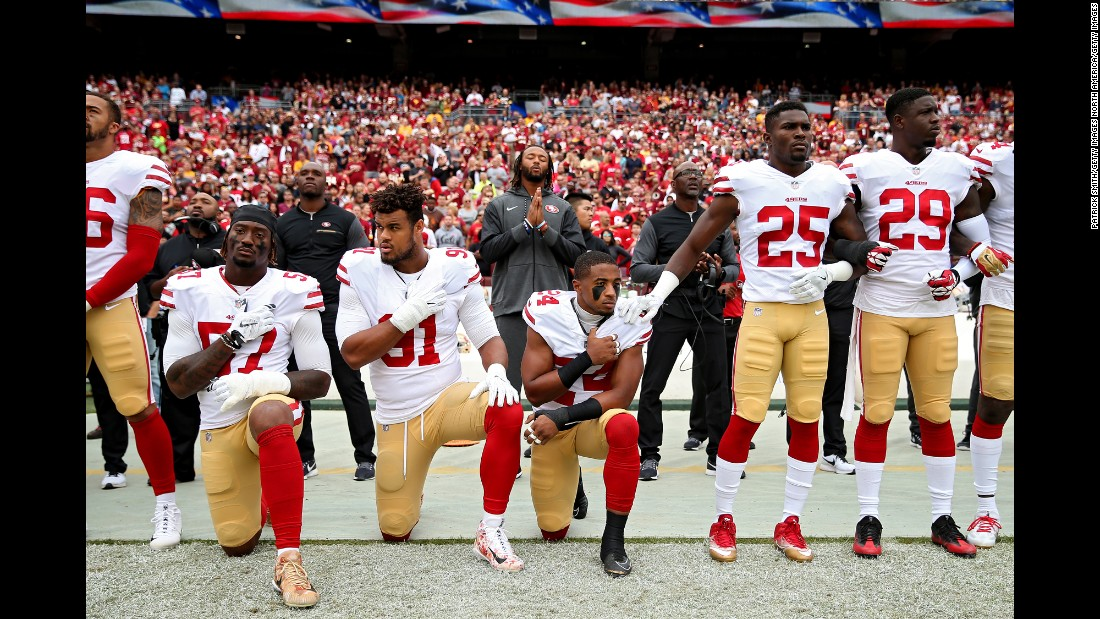 K'Waun Williams, Arik Armstead, and Eli Harold of the San Francisco 49ers kneel while holding their hands over their chest during the National Anthem before playing against the Washington Redskins at FedExField on Sunday, October 15, in Landover, Maryland.